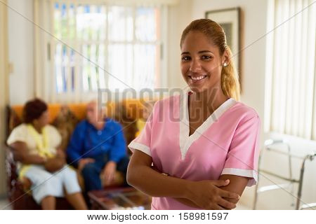 Portrait of girl at work as nurse in medical clinic for seniors. Happy worker smiling at camera in hospice.