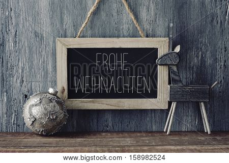 a wooden-framed chalkboard with the text Frohe Weihnachten, Merry Christmas written in German, a christmas ball and a cozy wooden reindeer, on a rustic wooden surface