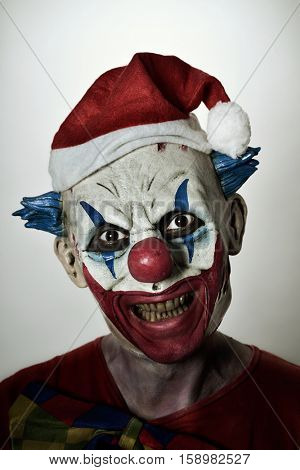 a scary evil clown wearing a santa hat with his mouth open showing his rotten teeth staring at the observer