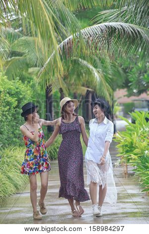 younger asian woman group relaxing with happiness emotion in garden in raining day