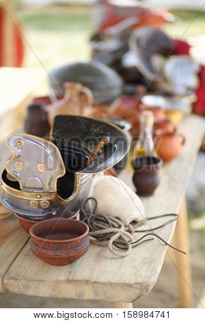 MOSCOW - JUN 06, 2015: Helmet Roman soldier on a wooden table near the household utensils at the festival Times and epoch: Ancient Rome in Kolomenskoye