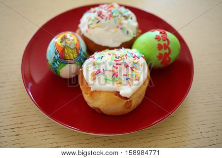 MOSCOW - APR 12, 2015: Colorful Easter egg with the inscription Grand Duke John and cakes on a red plate on a wooden table