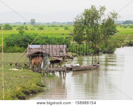 House on stilts at the riverside of the Kaladan River near Mrauk U in the Rakhine State of Myanmar. Rice fields in the background. Solar panel on the roof of the house.