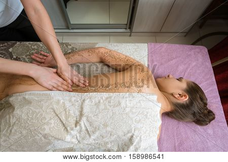 In spa salon. Top view of girl getting procedure body scrub