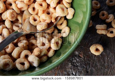 A top view image of a bowl of cereal with some cereal spit on the table top.