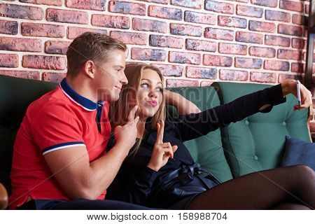 Close-up view of positive and funny young couple making selfie. Girl is puckering lips and looks pretty. Man showing ok sign