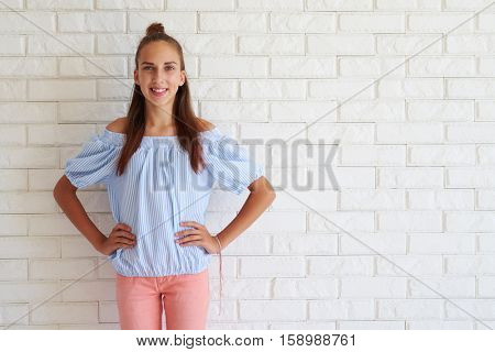Smiling pretty girl with arms on hips against white background. Wearing a casual outfit and with a bun posing at the camera