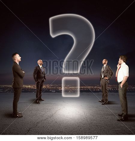 Team of businesspeople watch together a big question mark