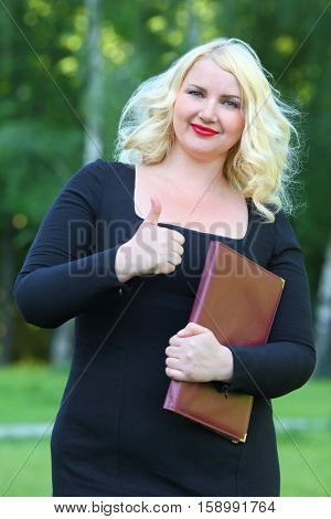 Happy business woman in black dress with a folder showing gesture thumbs up in front of green foliage