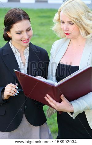 Two business woman looking into open leather folder in front of green grass