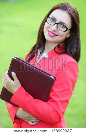 Happy business woman in red jacket with leather folder in front of green grass