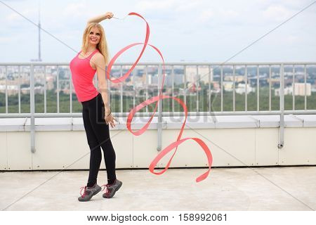 Happy beautiful blonde with red curly ribbon standing on tiptoe on the roof of a multistory building