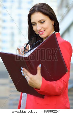 Business woman in red jacket looking attentively in open leather folder in front of multistory building