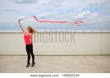 Beautiful blonde with red curly ribbon standing on tiptoe on the roof of a multistory building against the sky