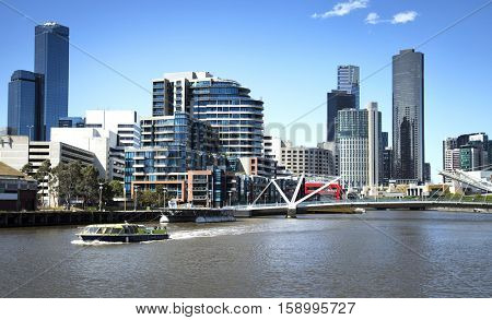 Touristic boat on Yarra river with downtown Melbourne in background in Australia