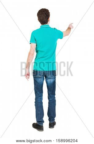 Back view of  pointing young men in  shirt and jeans. Young guy  gesture. Rear view people collection.   The guy in a stylish T-shirt shows the left hand