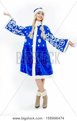 The Snow Maiden in blue Christmas costume. Beautiful white girl with long blond hair braided in pigtails. On her feet wearing suede brown boots. Makeup on the face and blue nails. Isolated on white.