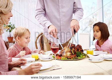 Mother and children looking impatiently for father carving roasted turkey
