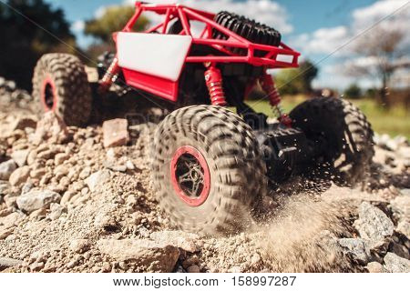 Rc suv pulling through rocky landscape. Small crawler riding on dry mountain road. Extreme sport, adventure, leisure concept