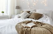 coziness, comfort, interior and holidays concept - cozy bedroom with bed and christmas garland lights at home poster