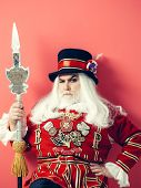 Frown senior man beefeater yeomen warder or male royal guard bodyguard in uniform with spear on red wall poster