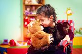 cute little girl in wheelchair telling her secret to plush bear in kindergarten for kids with special needs poster