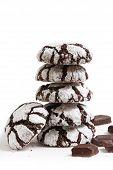 Stack of homemade chocolate crinkles cookies powdered sugar and pieces of chocolate on white background. Shallow focus. poster