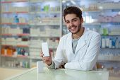 Friendly male pharmacist dispensing medicine holding a box of tablets poster