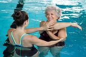 Young trainer helping senior woman in aqua aerobics. Senior retired woman staying fit by aqua aerobics in swimming pool. Happy old woman stretching in swimming pool with young trainer. poster