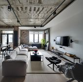 Sitting-room in a loft style with white and brick walls and a concrete ceiling. There are light sofas, wooden tables, different chairs, armchair, TV, lamps. On the floor there is a parquet and carpet. poster