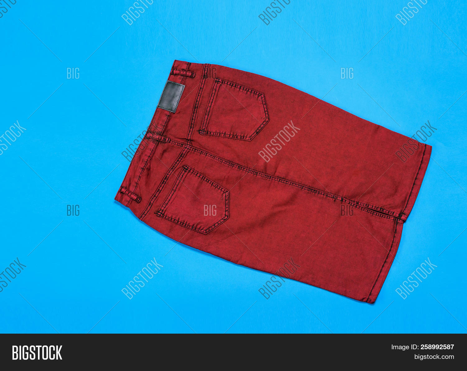 c39e5a0fc Burgundy denim skirt on blue background. Fashionable denim women's  clothing. Denim women's clothing on colored background.