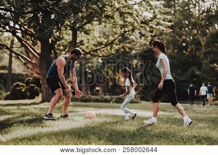 Happy Young Family Have Fun Outdoor In Summer Park. Sport And Healthcare Concept. Summer Park. Fun O