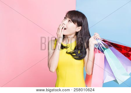 Woman Feel Surprise And Take Shopping Bag Happily On The Blue And Pink Background
