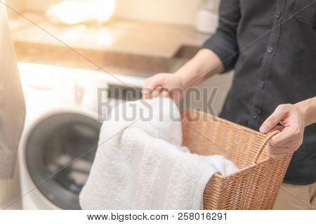 Male Hand Holding Wooden Laundry Basket With White Towel Inside Near Washing Machine In Laundry Room