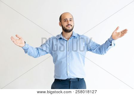 Content Man Spreading Arms And Greeting Someone. Positive Guy Looking At Camera. Friendliness Concep