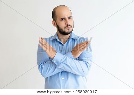 Strict Man Showing Crossed Hands And Looking At Camera. Guy Frowning And Denying Something. Prohibit