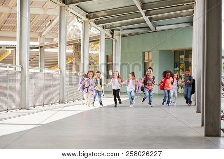 Primary school kids run holding hands in school corridor