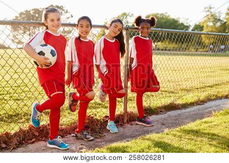 Four pre teen girls in a soccer team looking to camera