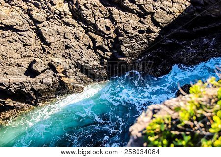 Aqua Clear Ocean Washing Onto Rocky Beach, Summer Day View From Cliffs Into Clear Tropical Water, Ro
