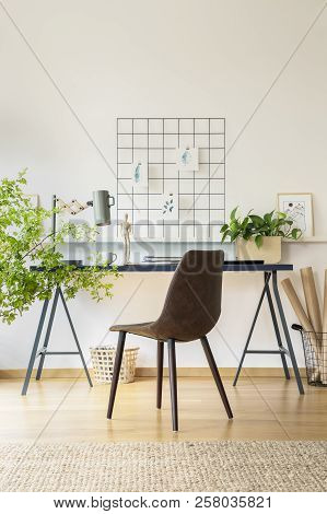 Real Photo Of Workspace Desk With Notebooks, Metal Lamp And Fresh Plant In White Room Interior With