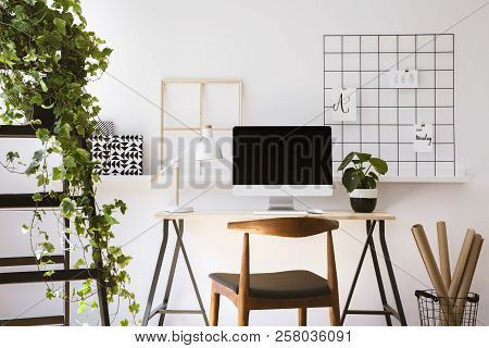 Real Photo Of Wooden Desk With Metal Lamp, Fresh Plant And Empty Screen Monitor Standing In White Fl