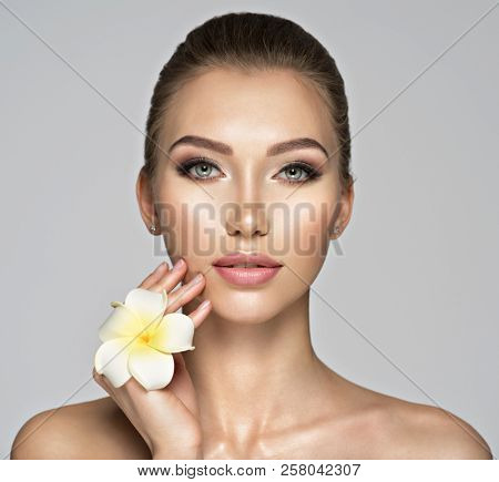Closeup face of  beautiful young woman with flower. Beauty treatment concept. Portrait of a pretty  caucasian girl with healthy skin.