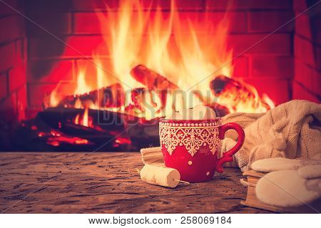 Mug Of Hot Chocolate Or Coffee With Marshmallows In A Red Mug On Vintage Wood Table In Front Of Fire