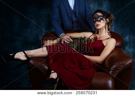 Rich Woman Female In Expensive Red Dress And Dark Carnaval Mask Sitting In Leather Sofa And Seductio
