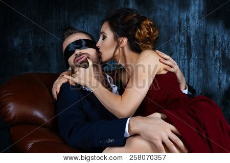 Couple In Dating. Rich Man Male Dress Suit With Tied Eyes By Black Tie Tempts Woman Female In Expens
