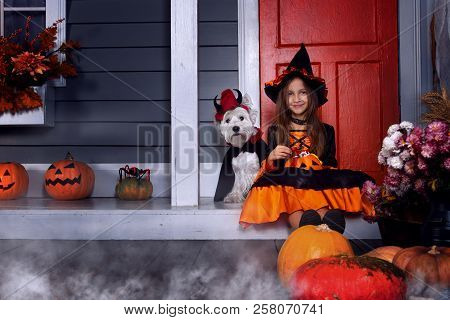 Young Funny Girl Child Kid In Halloween Orange Costume Playing Outdoor With Spooky Jack Pumpkins Wit