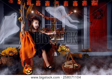 Funny Girl Child Kid In Halloween Witch Costume With Black Hat And Orange Lantern Pumpkins With Spoo