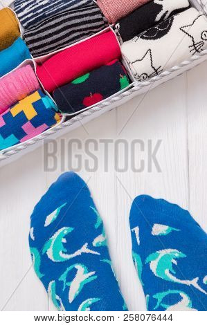 Box With Different Colorful Socks. Feet Selfie And A Socks Organizer On A White Wooden Background. T