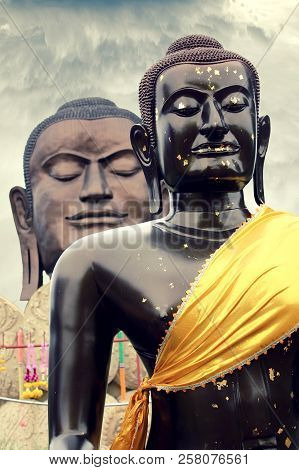 Dark Brown Budha Statue With Another Budha Looking Over His Shoulder