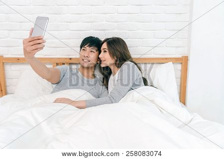 Happy Asian Lover Using The Technology Smart Phone For Selfie On The Bed In Bedroom At Home, Couple